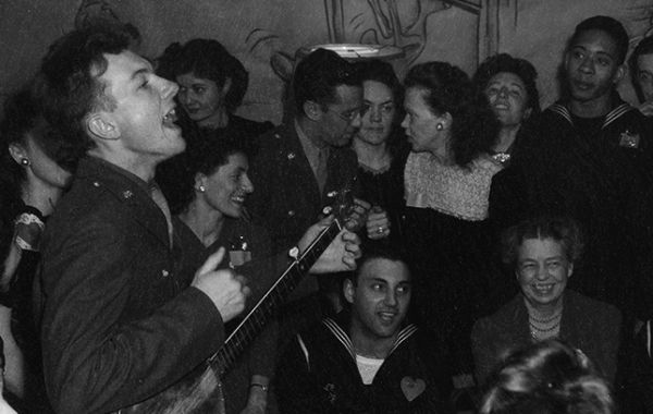 Pete Seeger performing on February 13, 1944, at the United Federal Labor Canteen, with First Lady Eleanor Roosevelt in attendance.